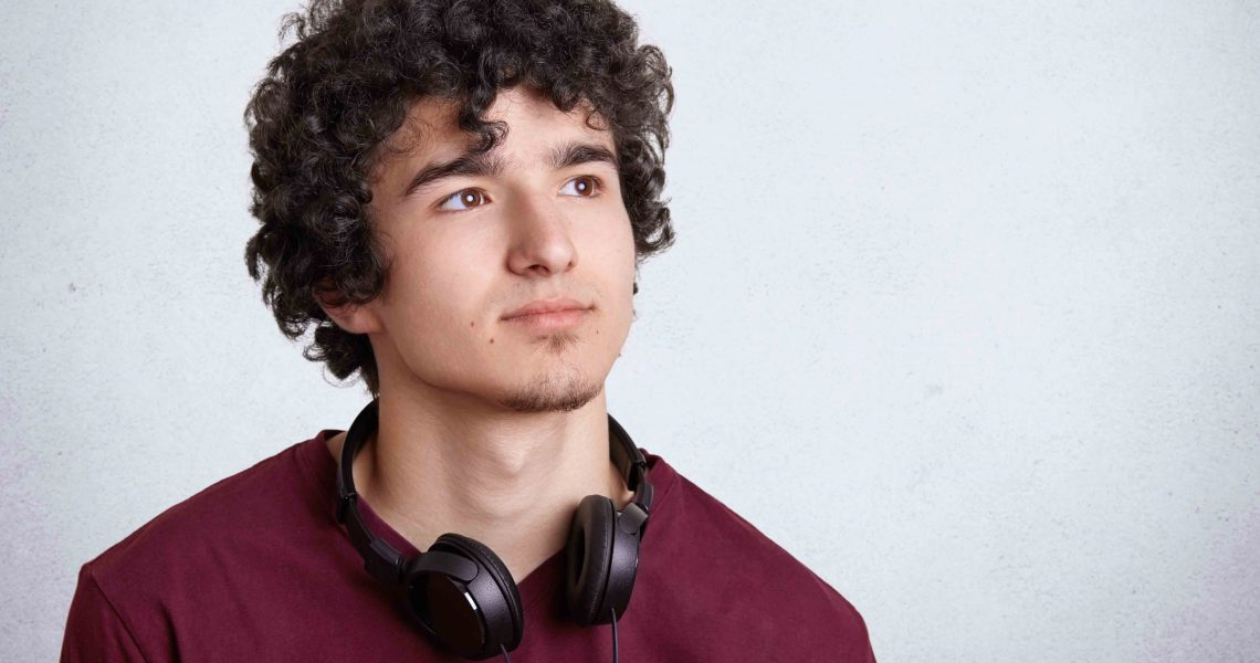 Portrait of serious pensive curly male teenager with curly hair, uses modern headphones for listening favourite music, looks pensively aside, isolated on white background with blank copy space