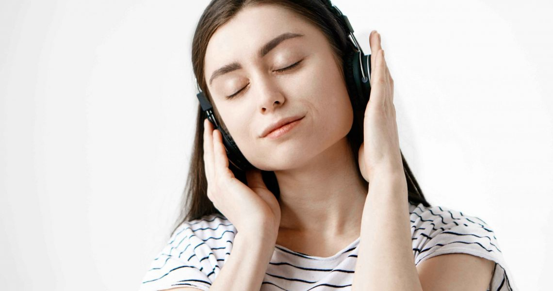 Music, meditation and relaxation concept. Studio shot of attractive brunette student girl posing with eyes closed, listening to calm meditative sounds of nature or ambient tracks using headphones
