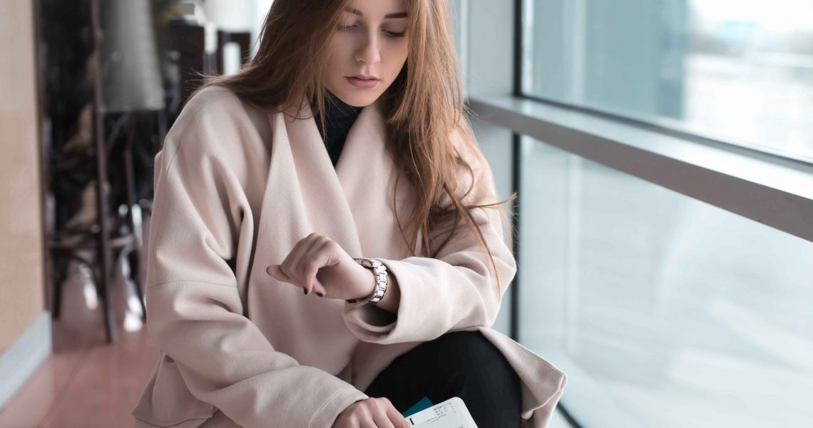 Young woman in international airport, waiting for her flight, checking her wrist watch and looking upset or worried. Arrival, missed, canceled or delayed flight concept.